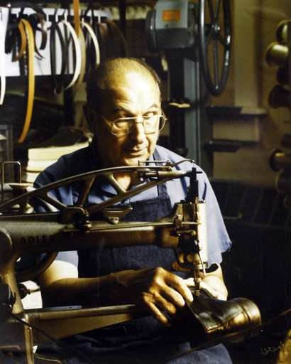 A photo of Carl Weinrich at work on the old sewing machine.