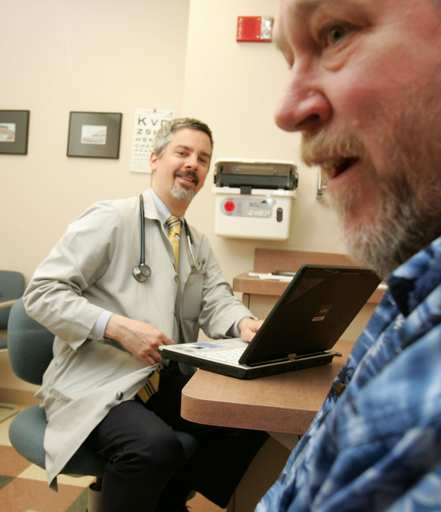 Dr. Joseph Kaliski uses a laptop computer to record symptoms from patient Tim Kunzendorf of Glen Ellyn. The information goes into an electronic database at the Elmhurst Clinic.