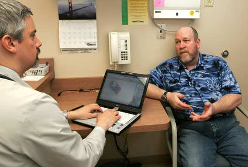 Dr. Joseph Kaliski uses a laptop computer to take notes from patient Tim Kunzendorf of Glen Ellyn. The information goes to an electronic database that authorized doctors can call up instantly anywhere in the world.