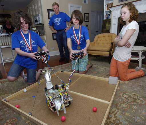 From left, Jacki Rohde,14, and Madeline Hume,14, with Rebekah Kiner,12, and teacher Andy Anderson control the robot on the obstacle course.