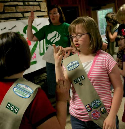 Lea Schultz, 15, recites the Girl Scout Promise with Cathy Riehs, left, of Naperville, who founded the special-needs Girl Scout troop with the help of WDSRA.