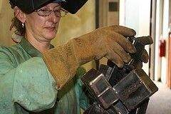Harper Continuing Education instructor Pamela Olin holds a welding tool and prepares to work. Olin is teaching two new classes at Harper this fall: