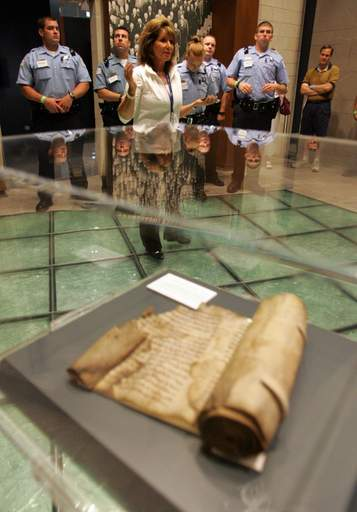 Volunteer Doris Lazarus leads police officers and firefighters on a tour of the Holocaust Museum in Skokie, part of a conference on the role of law enforcement in the Holocaust. In the foreground is Purim scroll saved from a burning synagogue on Kristallnacht in 1938 in Germany.