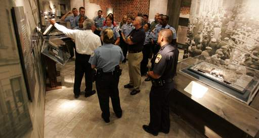 Police officers and firefighters from Chicago and the suburbs tour the Warsaw ghetto display at the Holocaust Museum in Skokie.