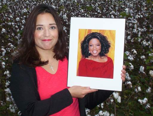 Oprah fan Monica Love, 35, formerly of Roselle, holds up an autographed photo she got while visiting Harpo Studios recently. Love says Oprah helped her change her life.