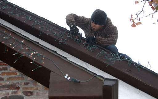 Sam Hernandez of Frosty's Holiday Lighting installs lights along the roofline of the McAlvany's Park Ridge home.