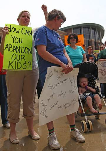 Robin Hooper, left, of Woodridge holds onto a protest sign and chants with other supporters of the Ray Graham Association in a courtyard outside the DuPage County courthouse on June 19, 2009.