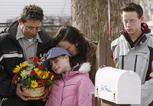 Joel's parents, Lloyd and Faith, along with his sister Grace, 10, and brother Nathan, 14, share a moment of prayer with everyone gathered in front of their home Friday morning in Elgin.