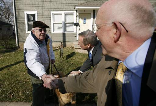 Jim Kelly, left, of Elgin meets Mayor Ed Schock, right, and U.S. Sen. Dick Durbin, who was visiting Elgin on Tuesday to talk about the foreclosure crisis. Kelly, a lifelong resident, was walking his dog Lucky.