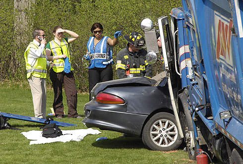 Officials stand by while the Sugar Grove firefighters remove a body from an accident on Route 47 near the entrance to Waubonsee Community College in Sugar Grove on Wednesday.