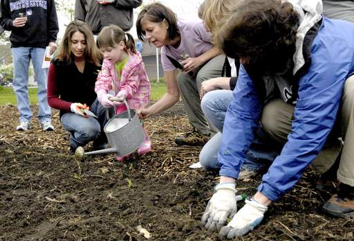 Julie Kotalik of Batavia Enterprises, left, watches Colleen Calhoun, 3, of Batavia water cabbage plants with the help of Jennifer Echert at the ceremonial first planting of a Batavia community garden Saturday. Batavia Enterprises is donating the land for the gardening.