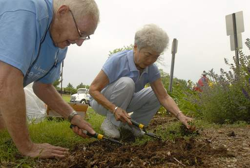 Friendship Village residents Tom Carroll and Ruby Hirakawa help with the weeding at Herbert Hoover Elementary School in Schaumburg.