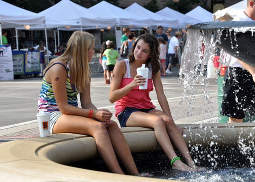 Kayle Campell, left, 13 and her friend, Morgan Pantone, 14, dip their feet in a fountain while enjoying some Biggby Coffee at the Taste of Arlington Heights Saturday evening.