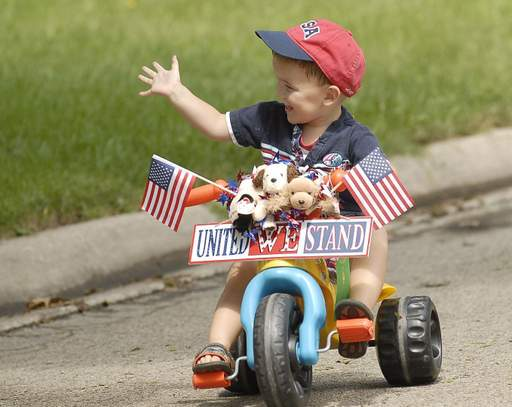 Three-year-old Oliver DeGroh waves to the crowd during the Pet and Bike Parade at Grayslake Summer Days.
