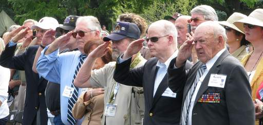 Vietnam Veterans salute during the playing of the Star Spangled Banner as the First Division Museum at Cantigny in Wheaton dedicated a restored Vietnam era Bell UH-1C/M helicopter gunship, better known as the Huey Saturday.