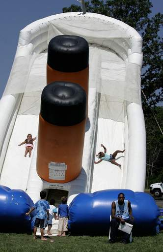 Naysa Rangai, 4, of Beach Park, left, and Zaniyz Cunningham, 4, of Waukegan slide down a ride called the Titanic during Greek Fest Sunday at St. Demetrios Greek Orthodox Church in Libertyville.