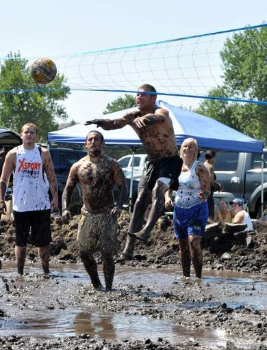 Participants struggle in the mud during the Elburn Days mud volleyball tournament Sunday.