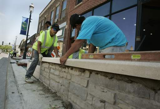 Silvano Gutierrez, left and Angel Gallegos of Sumit Construction adjust a cement piece Monday that will be part of one of the new flower planters along Main Street in West Dundee.