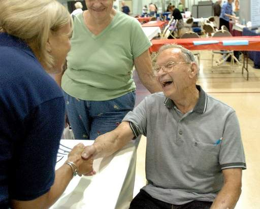 Fitness supervisor Karen Meserve congratulates Frank Thacker of Wauconda for his good body fat screening numbers during the Senior Fair at the Libertyville Sports Complex.