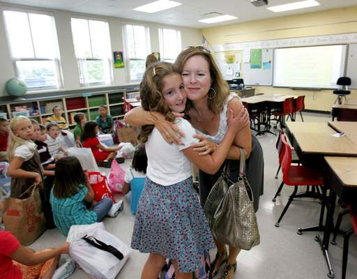 Julie Litfin gives her daughter Lauren a hug as she drops her off in her fourth-grade classroom for the first day of class at the new Wheaton Christian Grammar School in Winfield Tuesday.