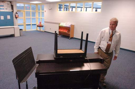 Principal Thom Gippert looks over a lonely piano in an empty music room on the first day of school at Deer Path School in Cary Elementary District 26. Music and art are some of the programs that were cut as the district struggles with financial difficulty.