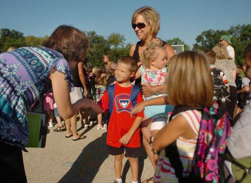 First grader Liam Waco and his mom Amy are greeted by teacher Nancy Siles on the first day of school at Deer Path School in Cary Elementary District 26.