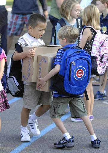 Bored from standing in line waiting to start school, second graders Zach Lew, left, and Lucas Hipp, both 7, wrestle with school supply boxes outside Western Avenue School in Geneva on Wednesday, August 25.