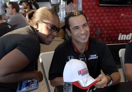Dona Crane of Chicago poses with Indycar driver Helio Castroneves at the autograph tent at Woodfield Mall on Thursday.