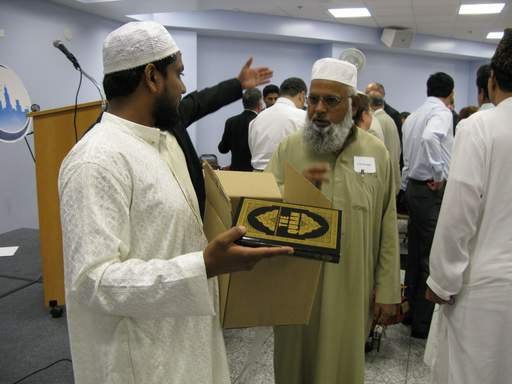 Abdul Sattar, left, and Ghulam Farooqie, president of the Islamic Community Center of Des Plaines, hand out copies of the Quran.