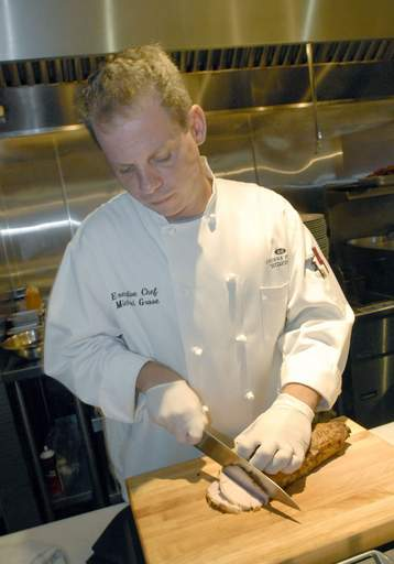 Chef Michael Grove slices roast pork for the Cuban sandwich at the Chicago Fire Oven restaurant in the Crowne Plaza O'Hare Hotel in Rosemont.