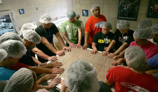 Elmhurst College students packed lunches for Feed My Starving Children. Above, part of the group prays over the meals, following the completion of their shift.