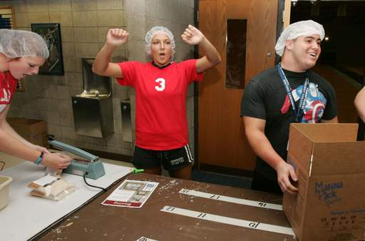 As part of freshman orientation, Elmhurst College students pack lunches for Feed My Starving Children. Hannah Lessen, center, lets out a cheer after packing the box carried away by Jake Zalka, right.