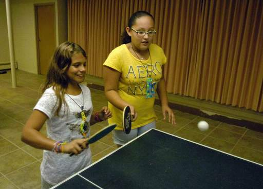 Eleven-year-olds Corsica Taylor, left, and Aliyah Gomez, both of Bensenville, play ping pong during a program in which Elmhurst College students give back to the community.