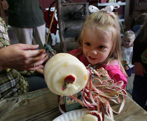 Ava Oldenburg, 2, of Linderhurst cores an apple as toddlers enjoy All About Apples during the Lake County Forest Preserve's Little Sprouts program Wednesday at the Bonner Heritage Farm in Lindenhurst.
