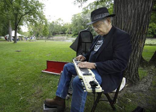 Dale Stallmann of Aurora sits under a tree and plays his steel guitar as he waits for a friend Monday at the Fox Valley Folk Music and Storytelling Festival in Island Park in Geneva. The guitar was found on the curb and Stallmann refurbished it.