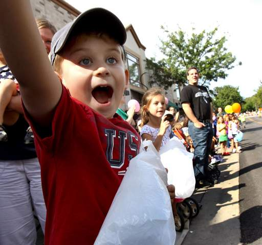 Tim Kasprzak, 6, gives a wave and a shout Monday as he spots his grandfather in the Naperville Last Fling parade in downtown Naperville. His grandfather is a member of the Naperville Municipal Band.