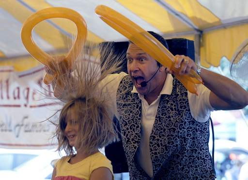 Randy Bernstein of Magic by Randy gives Sharon Zavlin, 9, of Buffalo Grove a new hairdo on the last day of Buffalo Grove Days Monday at Emmerich Park.