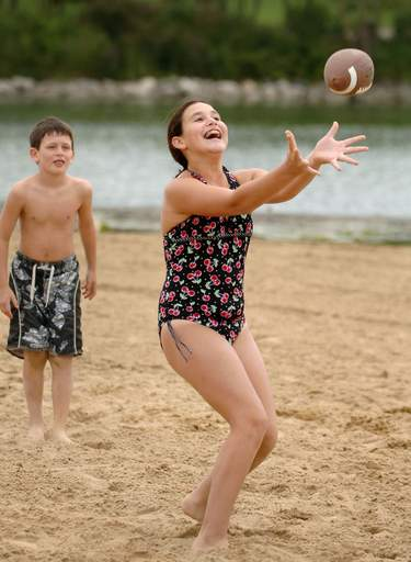 Maddie Orloff, 10, of Riverwoods successfully snags the ball from her cousin Jordan Krasner, 8, of Vernon Hills during a keep away game on the beach at Independence Grove near Libertyville Monday.