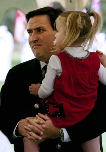 Firefighter of the Year John McNeill holds his daughter Annie, 2, during the national anthem at the Gurnee Breakfast Exchange Club 9/11 Remembrance Ceremony Sunday at Viking Park.