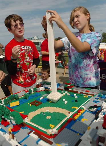 John Burke of Lake Zurich and Melanie Gackowski of Richmond build a tower on a Lego model of Alexian Field on display at the Flyers' Kids Zone at Alexian Field, home of the Flyers.
