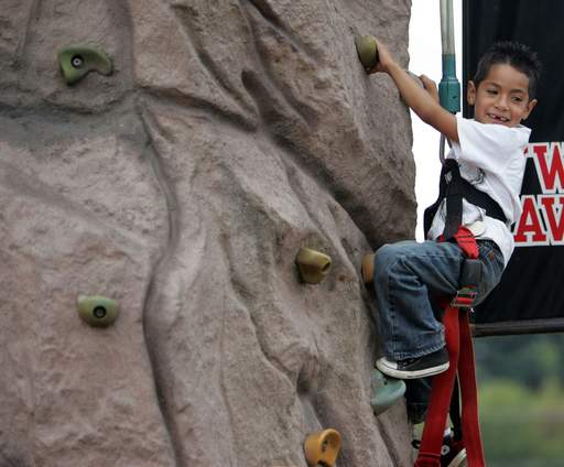 Five-year-old Gerado Morales, of Elgin, attempts some climbing during Elgin's Largest Block Party at Festival Park in Elgin.