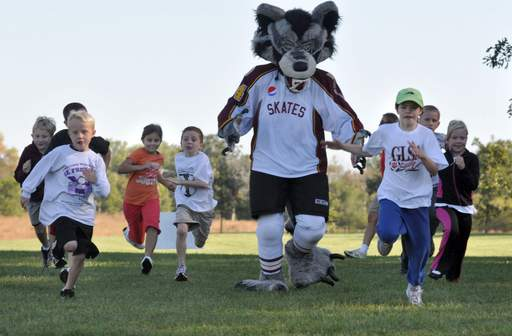 Chicago Wolves community relations assistant Dan Harris races with kids at the Run 4 Kids walk/run Sunday morning. The 5K race benefits the Lexi Kazian Foundation that helps improves the comfort and quality of life of special needs children.