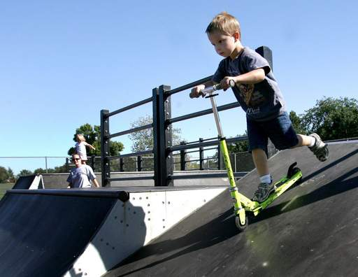 Although only five years old, Stefan Maca of Bloomingdale gets the hang of the ramps on his scooter during his first trip to a skate park Monday afternoon. His mom Karen Maca and sister Lily, 3 look on during their outing at Newton Skate Park in Glen Ellyn .