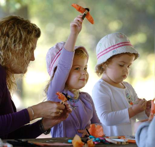 Julia Cleeton, 3 of Grayslake, makes her magnet butterfly take off during craft time with her mother, Melissa, and twin sister Lauren, right, during the Lake County Forest Preserve  Hikin' Tykes program at the Lakewood Forest Preserve near Wauconda.