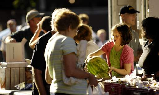 Cassie Kemmler, 13, a congregation member of First Congregational Church of Elgin, hands out a watermelon as she helps distribute food Tuesday evening for the Northern Illinois Mobile Food Bank. At least 200 families were served.