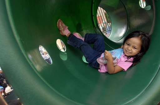 Ashley Noel, 4, of Wheeling, plays in the tube section of the playground equipment during the grand opening at the Wheeling Park District Preschool on Wednesday.