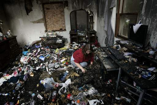 Polly Thorne of Carpentersville digs through the remains of her bedroom Thursday after fire destroyed it Monday night.