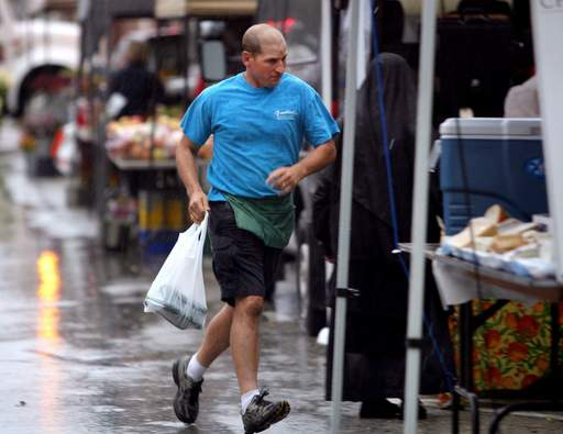 Dean Froehlich of Froehlich's Produce in Three Oaks, Michigan makes a dash for his van in the rain during the farmers market Thursday morning in downtown Libertyville.