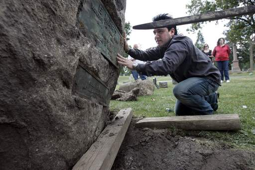 Terry Evanswood looks over the plaque that he was hoping to find on the large rock in North Cemetery.