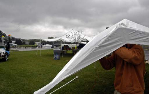 Joel Davidson of Harvard helps put up a tent that had been blown down more than once at the Heritage Farm Fest in Campton Hills Saturday. Many of the activities planned had been scaled back or canceled due to the nasty weather.